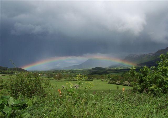 Paisaje del Valle de Mena con vistas de La Peña y praderías en plena tormenta con arcoiris.